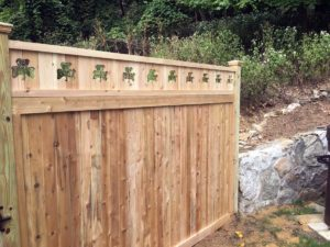 A wood solid panel fence with a top rail that has clover cutouts.