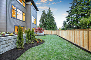 Luxurious contemporary three-story wood siding home exterior in Bellevue. Nice backyard landscape with well kept lawn flower beds and wooden fence. Northwest USA