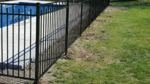 A black aluminu fence encloses a pool on a residential property.