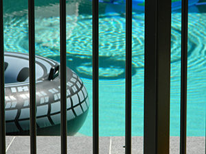 A swimming pool behind a safety fence
