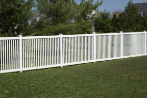 A new white vinyl fence by a grass area with trees behind it.