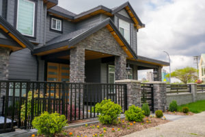Luxury residential house with front behind metal fence. Big family house with landscaped front yard
